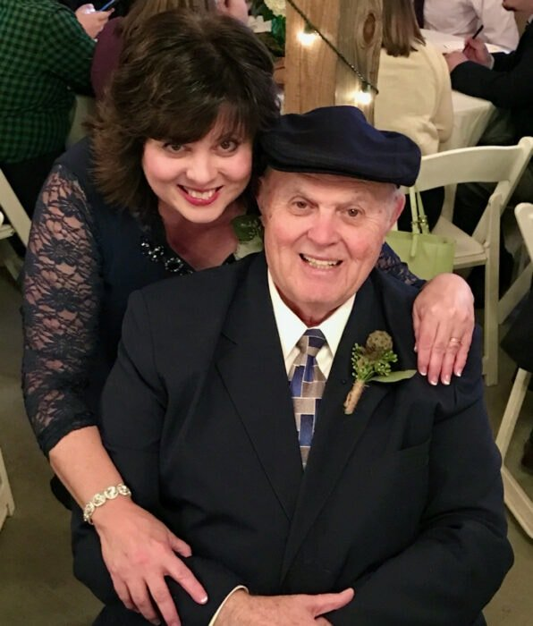 Debi embracing her father at her son's wedding while dad sits in chair