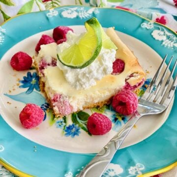 image of raspberry slab cheesecake on a blue rimmed plate with whipped cream and a lime slice