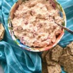 pimento cheese on a blue cloth with crackers beside it