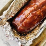 bbq ribs in aluminum foil coming out of the oven on a sheet pan