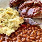 bbq ribs with potato salad and baked beans on a white plate