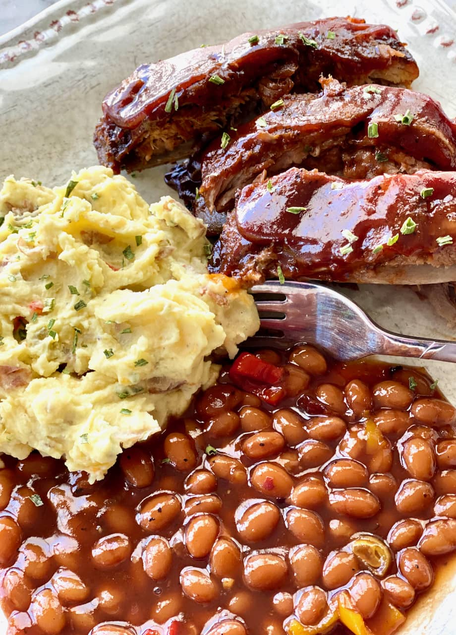 fall off the bone bbq ribs with potato salad and baked beans on a white plate