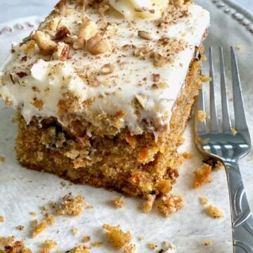 slice of carrot cake with icing and nuts on a white plate with a fork beside it