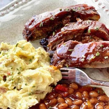 fall off the bone ribs served with potato salad and baked beans on a white plate.