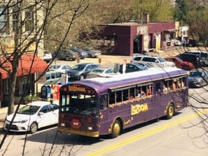 purple Lazoom Bus headed up the road on Biltmore Ave. in Asheville