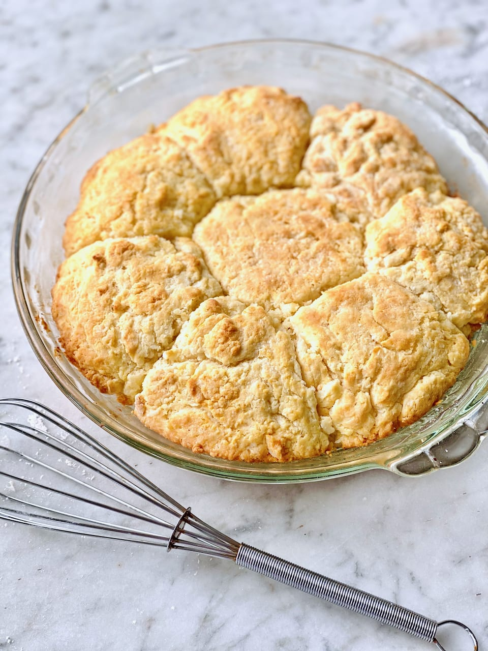 drop biscuits cooling in a glass pie plate on a white counter with a whisk beside them