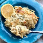 a fork of spaghetti with lemon and chicken on a blue plate