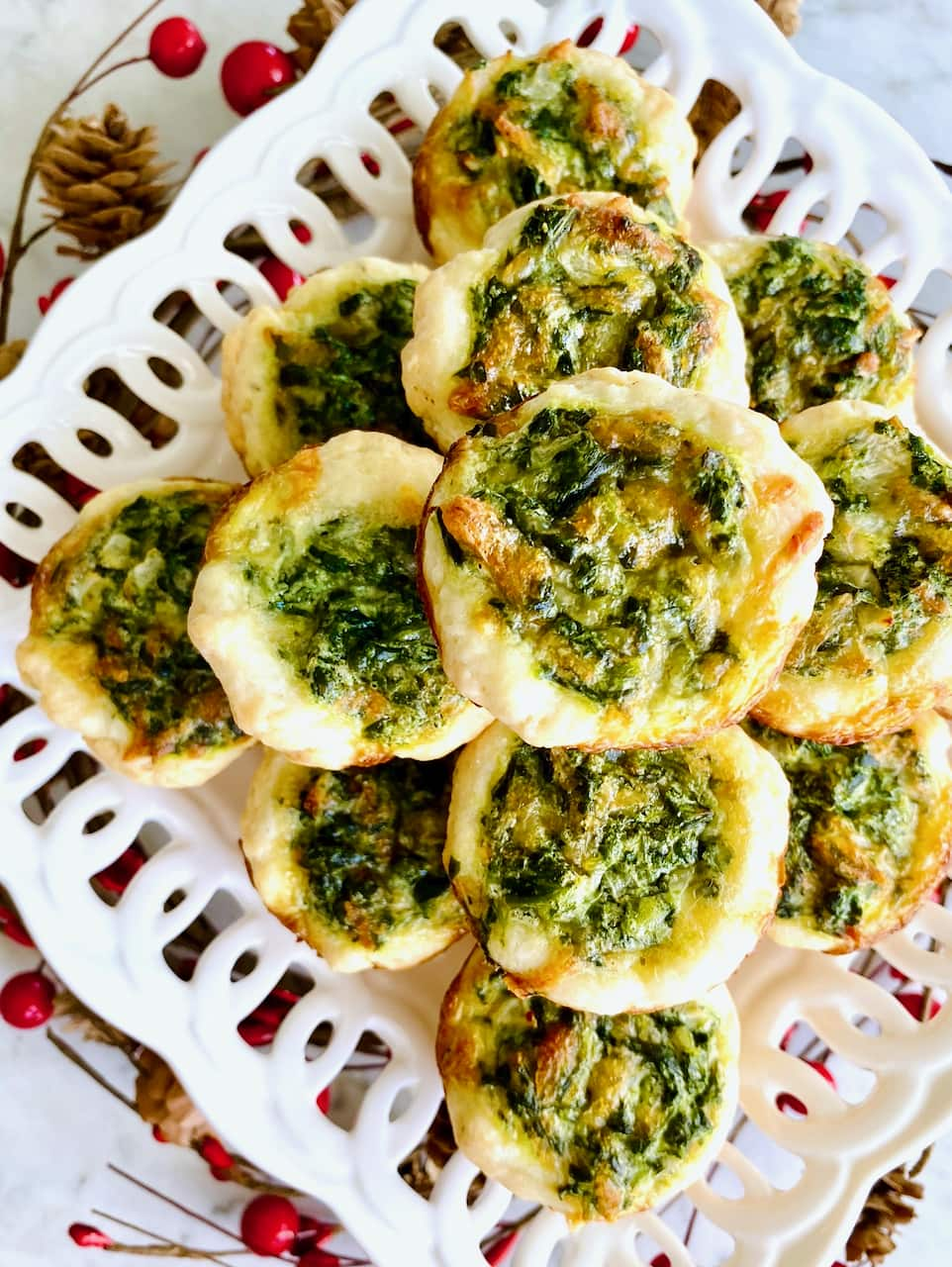 mini spinach quiches on a white lacy plate