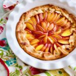 peaches arranged in a circle inside a crust on a white pie plate with peach jam