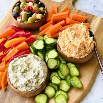 olives, pimento cheese and spinach artichoke dip with carrots, pepper and cucumbers on a wooden board