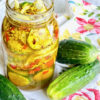 jar of bread and butter pickles with three cucumbers on a floral napkin