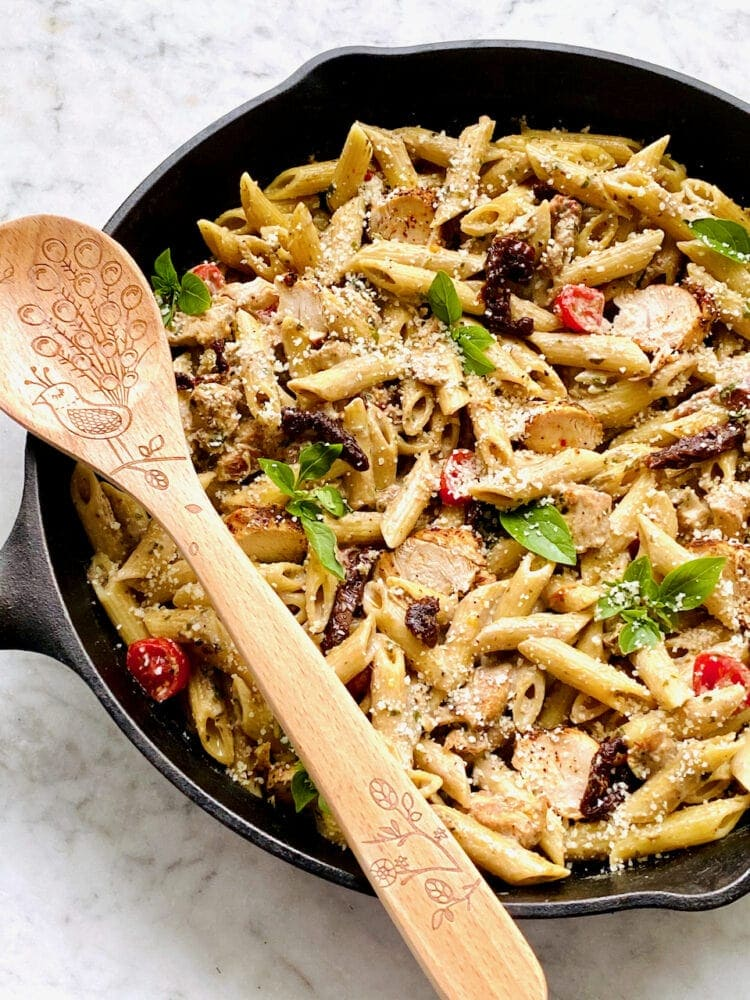 pesto pasta topped with chicken, tomatoes and basil with a wooden spoon in a cast iron skillet
