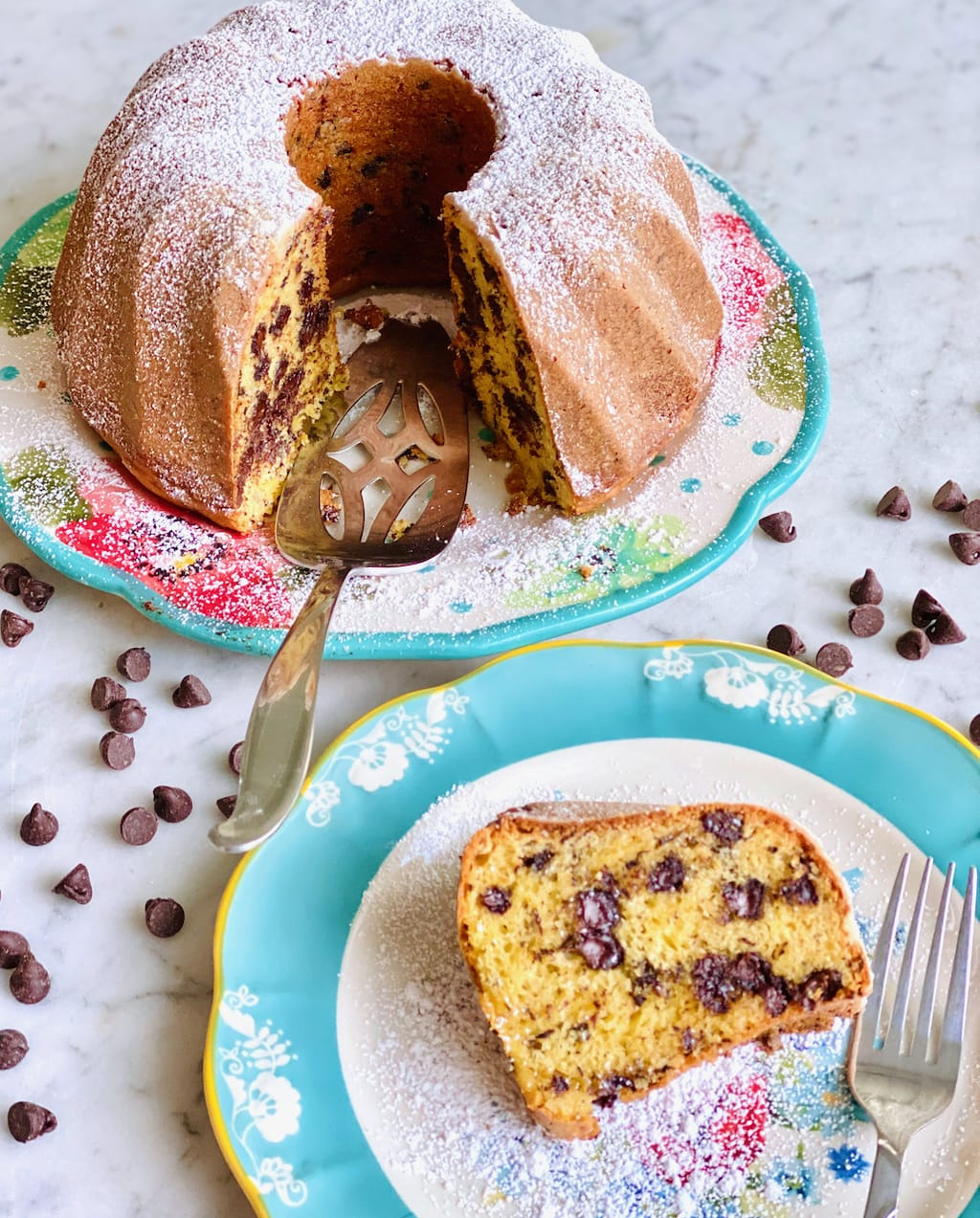 slice of chocolate chip cake on a plate in front of whole cake