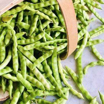greasy cut short beans spilling out of a farmer's basket laying on its side