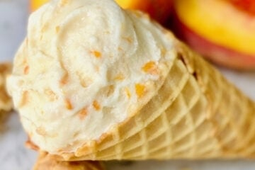 peach ice cream in a cone resting on another waffle cone