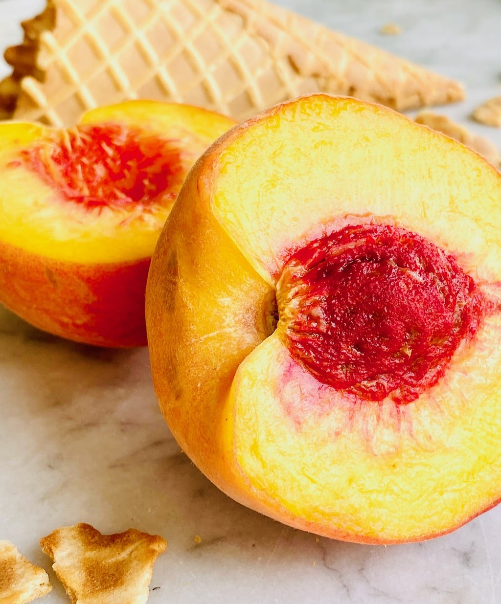 two halves of a freestone peach with waffle cone pieces behind it