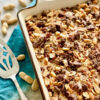 chocolate cake topped with peanuts, chocolate peanut butter cups in a white dish on a blue napkin