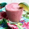pink smoothie cooler with berries and a lime wedge on glass rim on floral napkin
