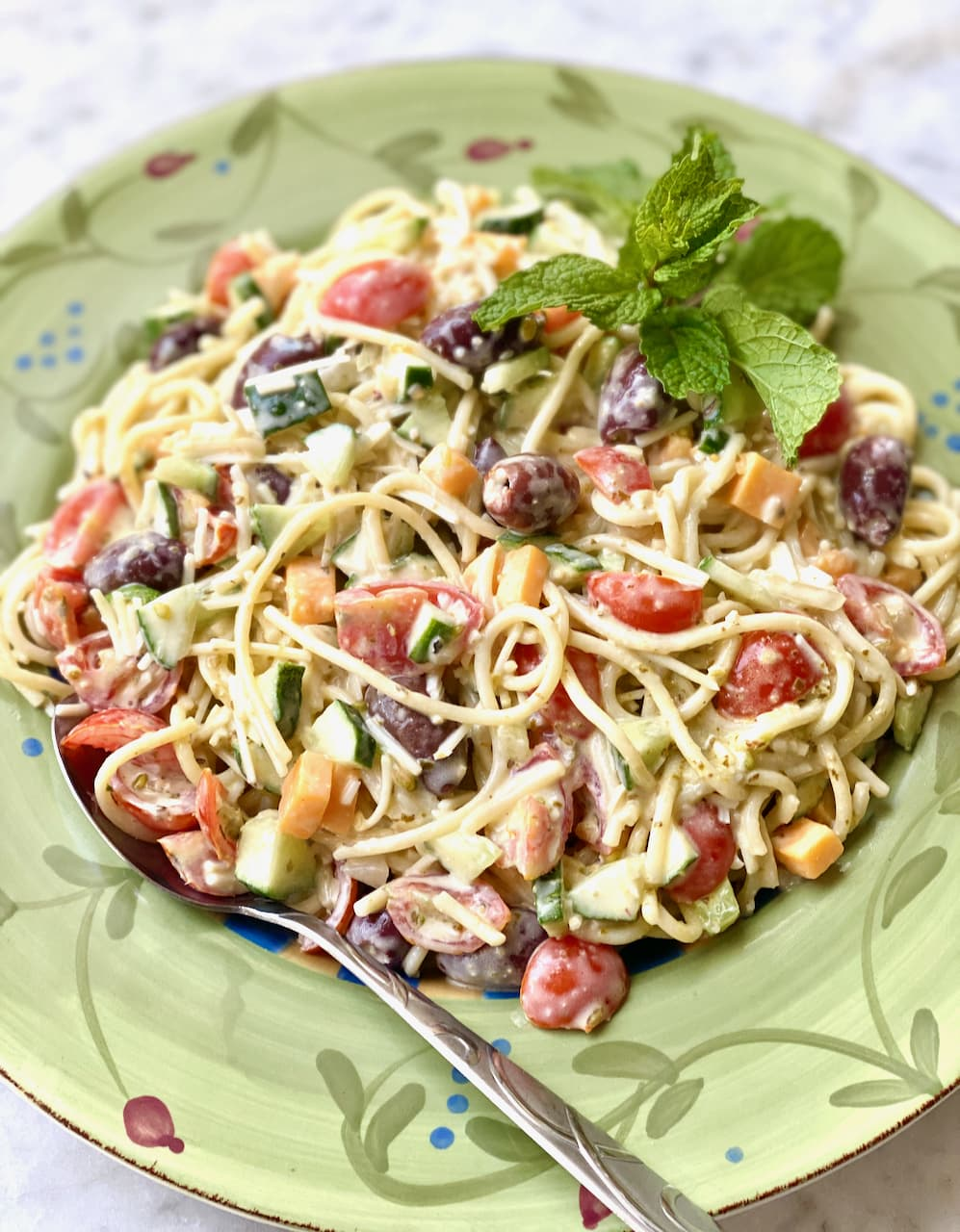 cold spaghetti salad with a variety of vegetables in a green bowl with a mint garnish