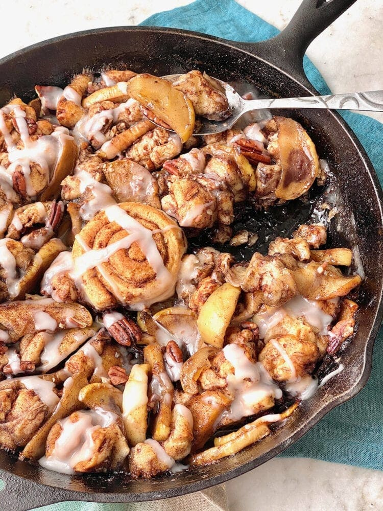 monkey bread apple cobbler in a cast iron skillet with a spoon taking a bite