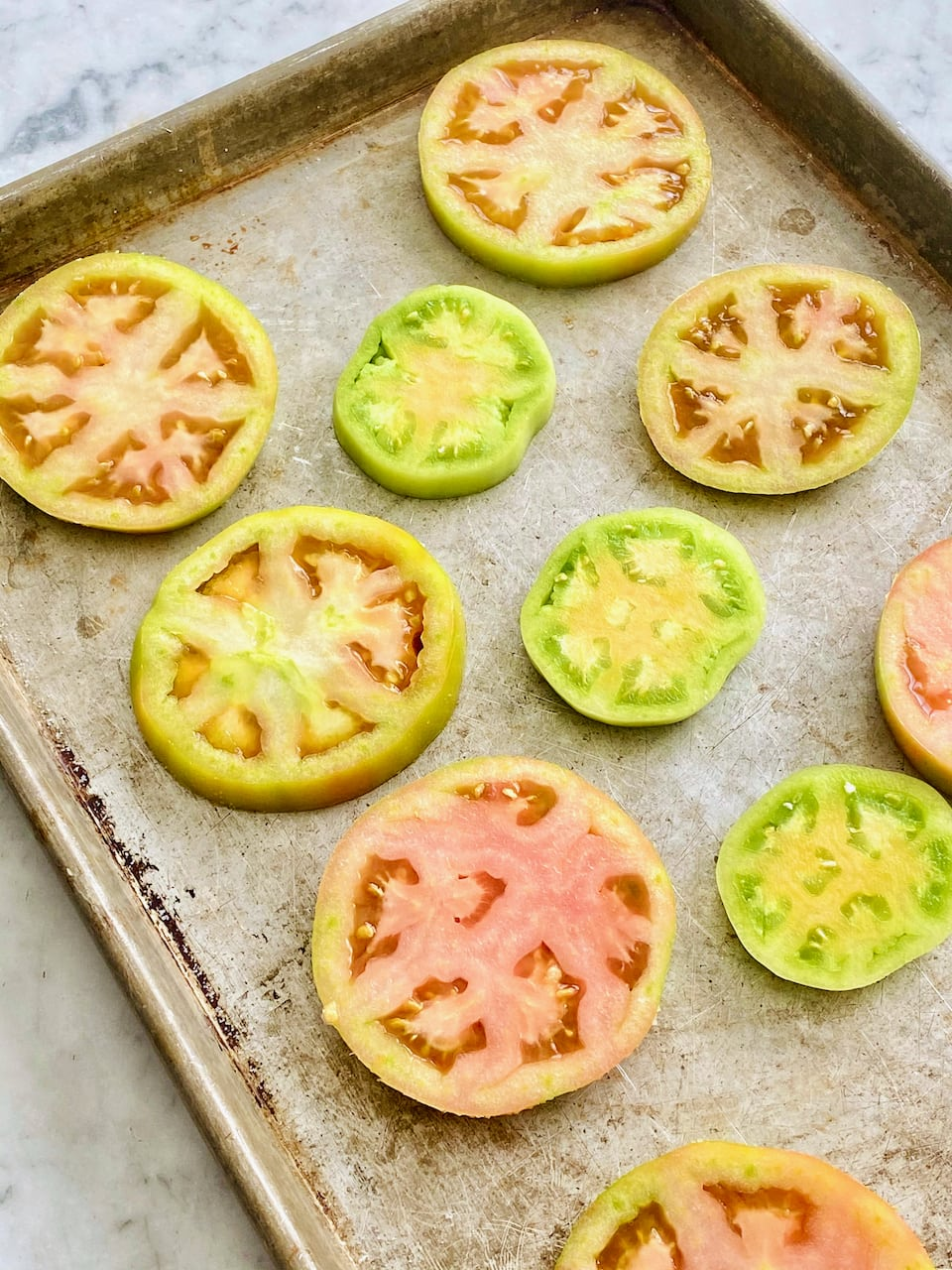 green tomatoes sliced in rounds on a sheet pan