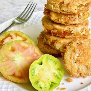stack of fried green tomatoes with unripened tomatoes on a white plate with a fork