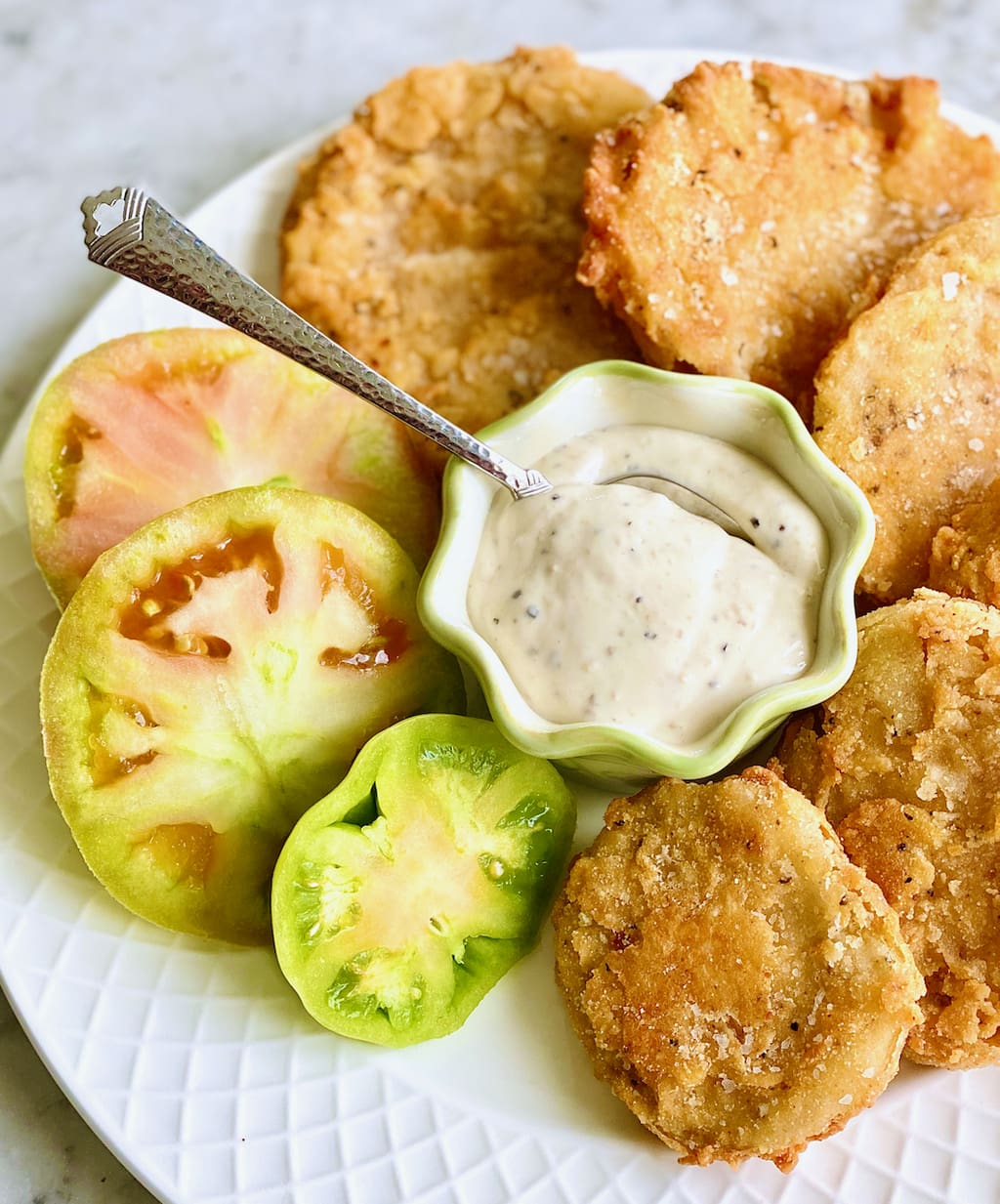 fried green tomatoes in a circular pattern with ranch dip in the middle