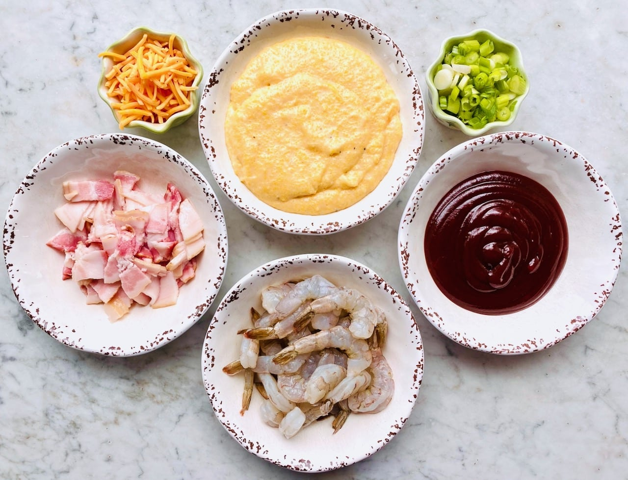 ingredients for shrimp and grits including bacon, shrimp, bbq sauce, grits, cheese and onions