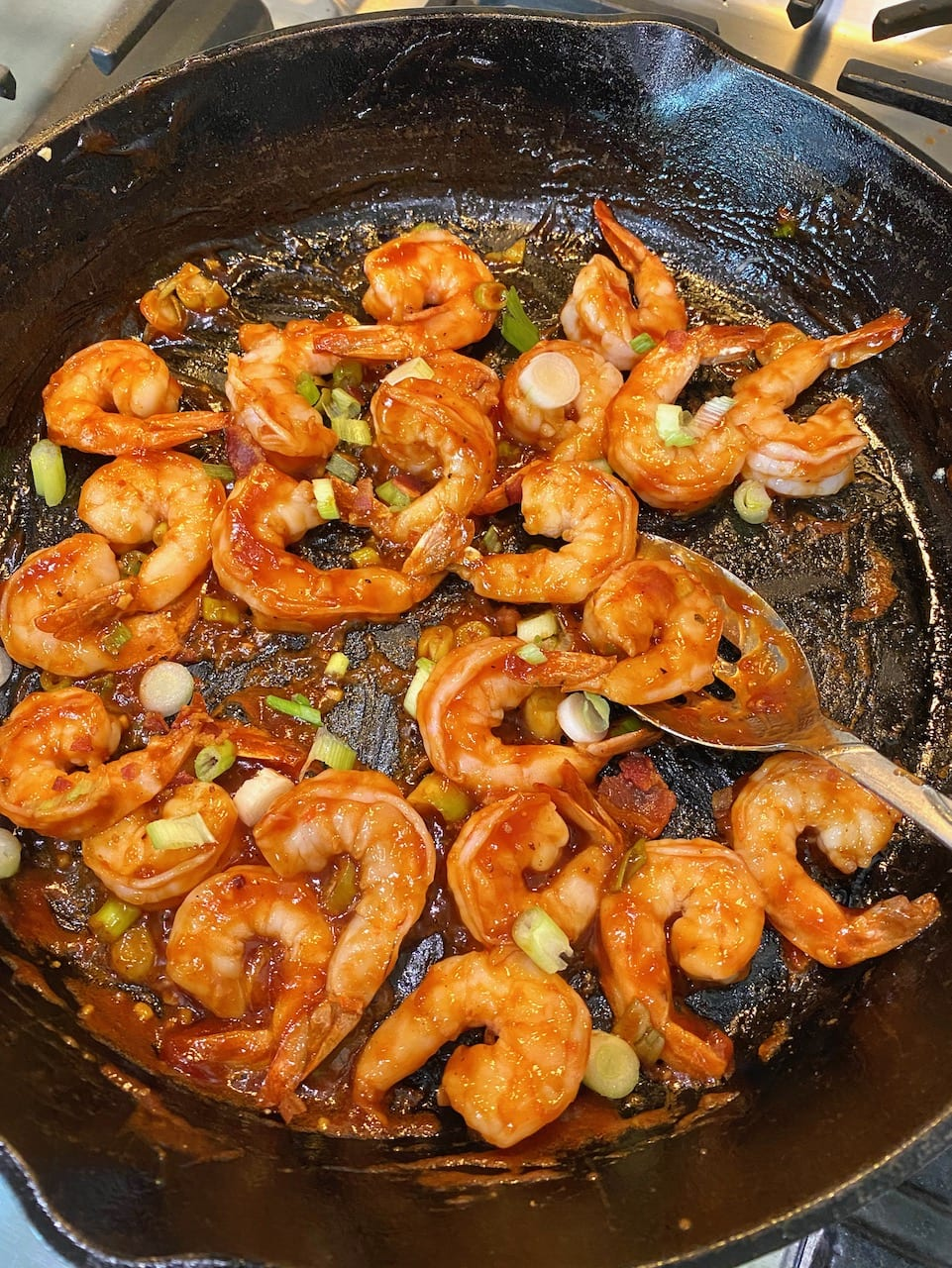 barbecue sauce covering shrimp in a cast iron skillet