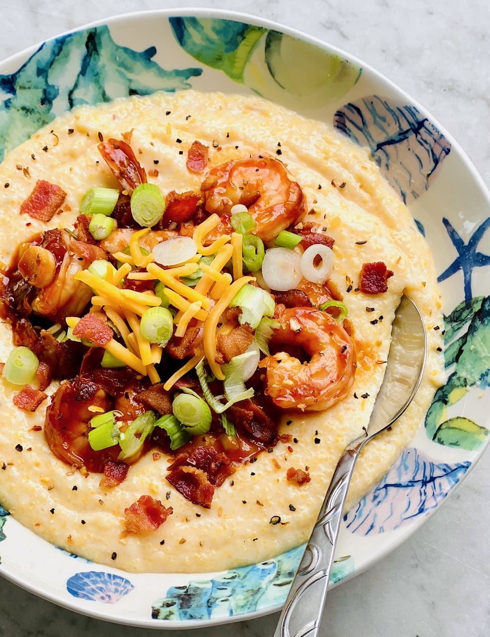 gouda cheese grits topped with BBQ shrimp, bacon and green onions in a seafood bowl