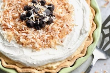 toasted coconut and chocolate on top of a coconut cream pie in a green plate.