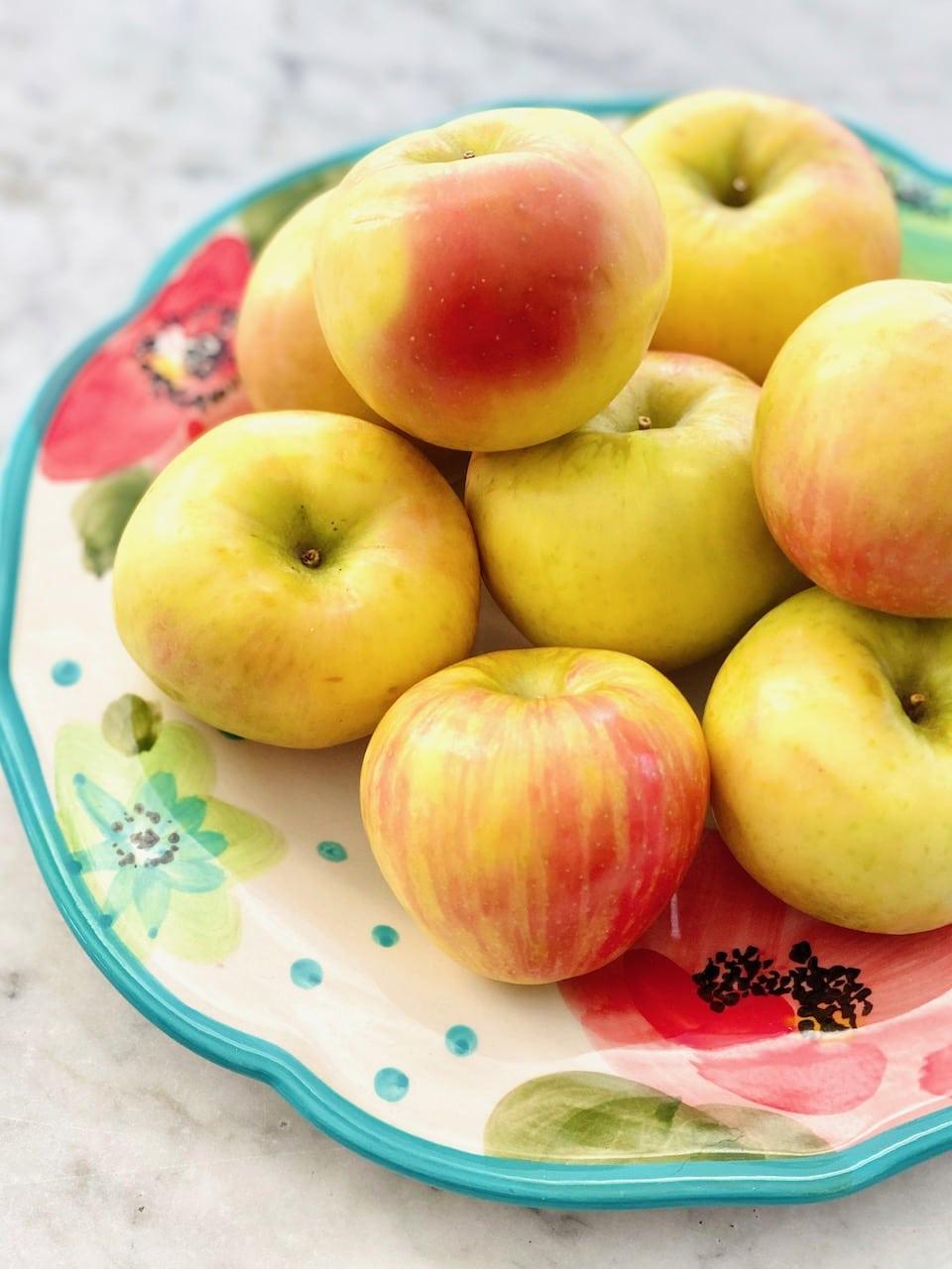 stack of honey crisp apples on a floral plate.