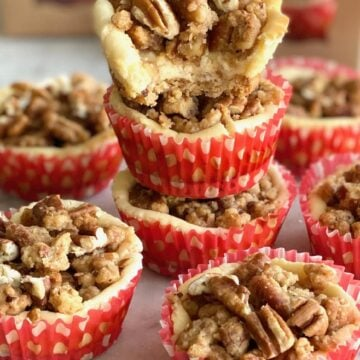 stack of Baileys Streusel Cheesecake Cups with top one missing a bite.