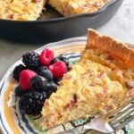 a slice of meat lover's quiche with berries on a plate and skillet in the background.