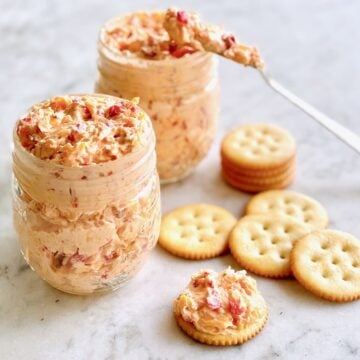 pimento cheese in mason jars with crackers and a spreader dipping in the cheese.