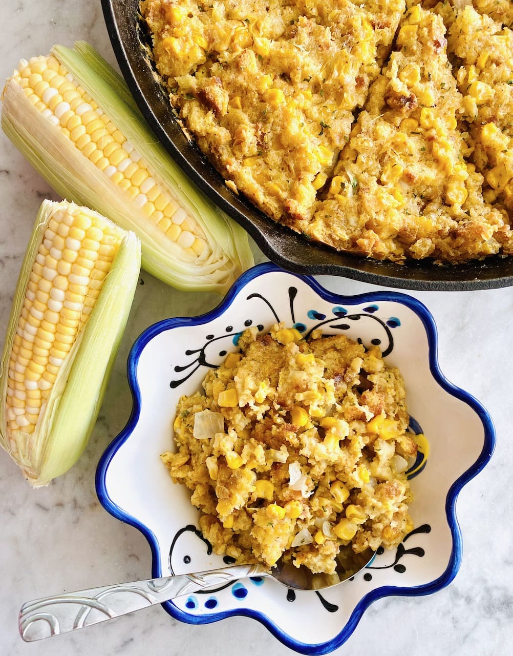 skillet of sweet corn casserole beside two ears of corn and a bowl full of casserole.