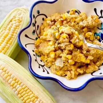 bowl of sweet corn casserole beside two ears of corn.