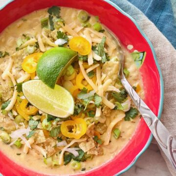 limes, peppers and cheese on top of a red bowl of white corn chicken chili