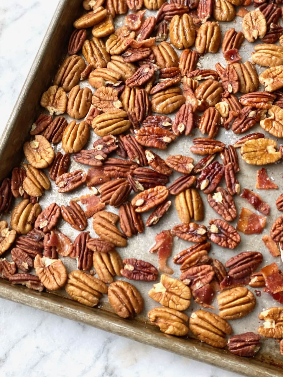 pecans and bacon on a sheet pan.