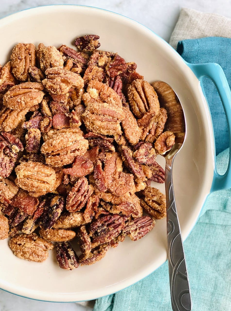 a spoon full of candied bacon pecans being scooped out of a bowl.