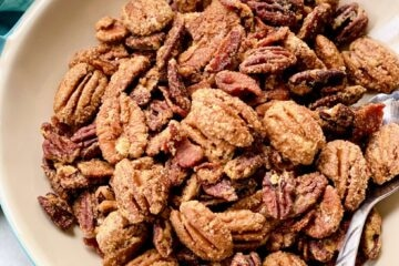 candied bacon pecans in a white bowl with blue handles.