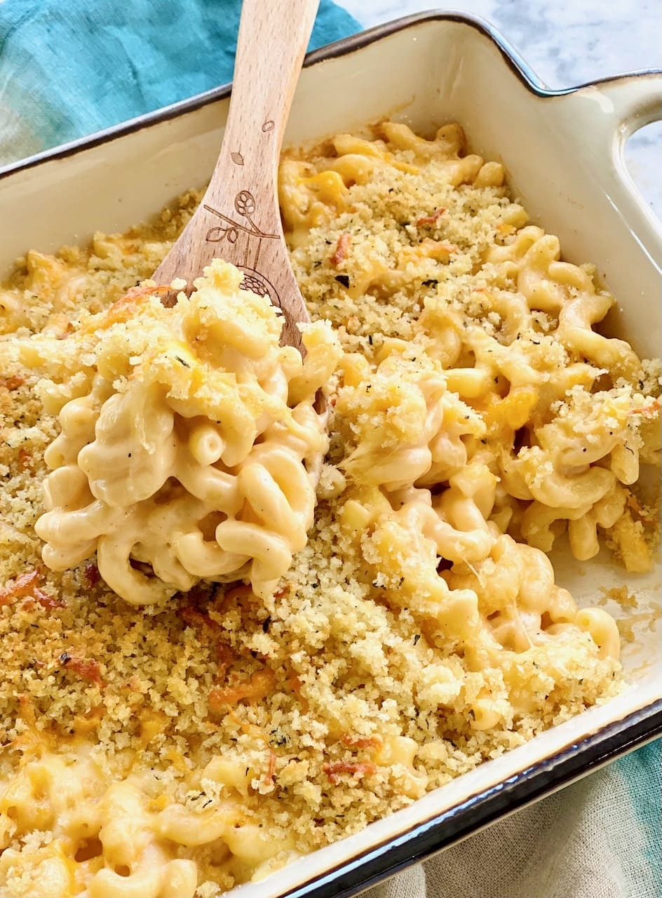 wooden spoon lifting a serving of homestyle mac and cheese out of a casserole dish.