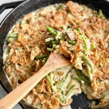 green bean casserole with fried onions and no cream of mushroom soup in a cast iron skillet.