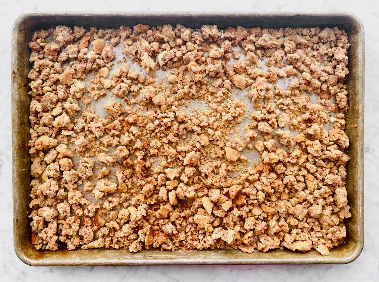 sheet tray filled with snickerdoodle cookie crumbles.