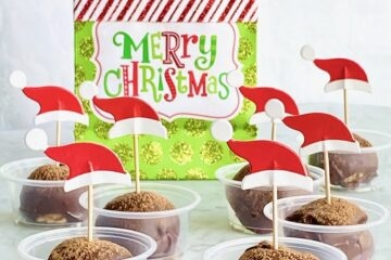 a merry christmas gift bag with truffles in front of it.