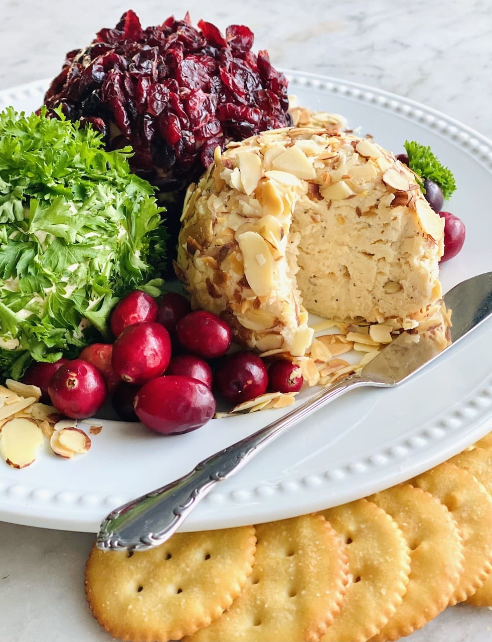 holiday cheese ball trio with slice cut out of almond ball.