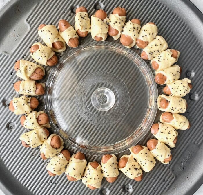 mini cocktail wieners wrapped in crescent rolls in a ring with poppy seeds
