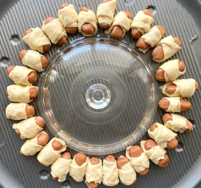 little cocktail wienies wrapped with crescent rolls in a ring around a glass bowl.
