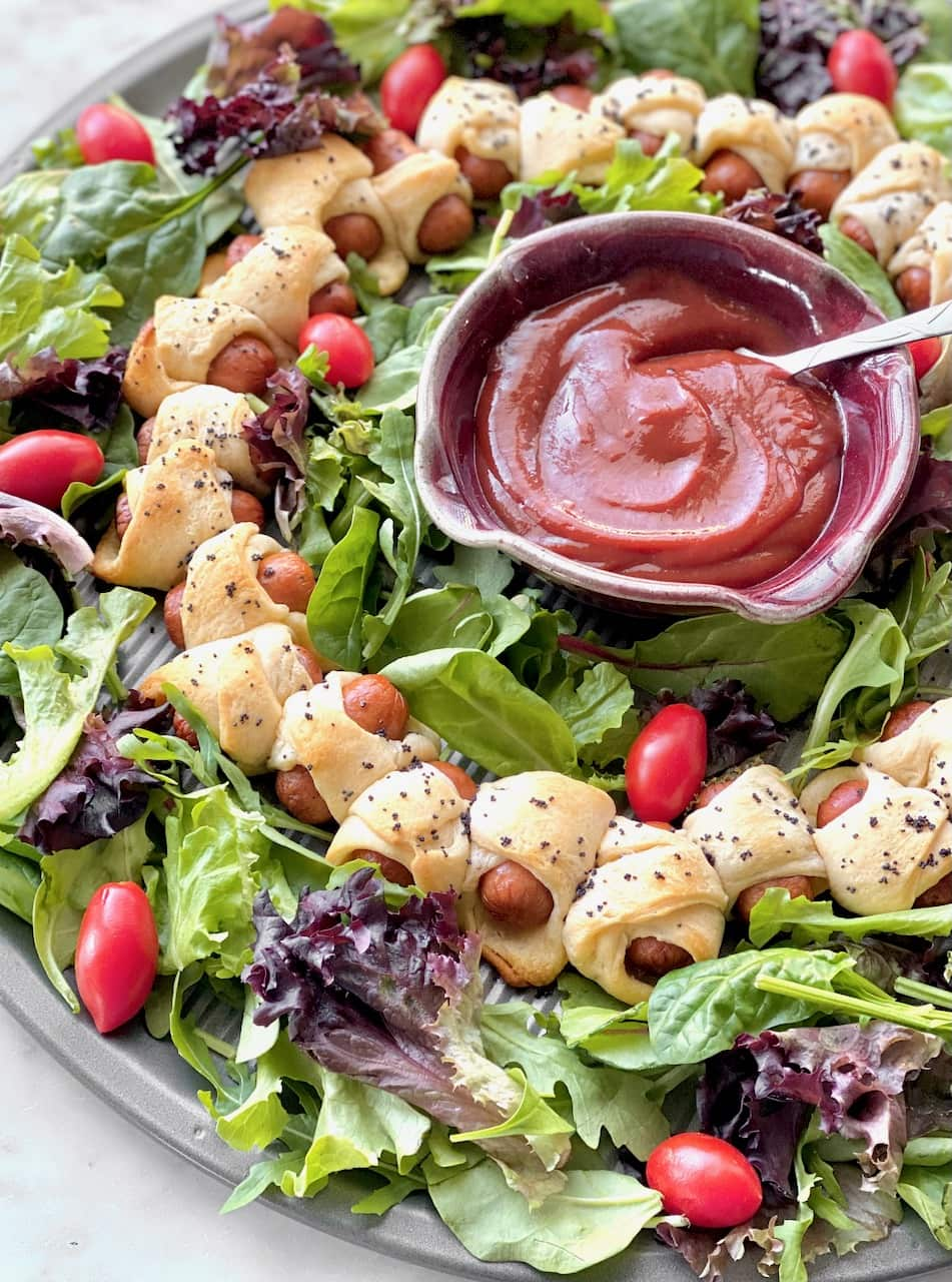 little pigs in a blanket on a bed of greens surrounding a bowl of bbq sauce.