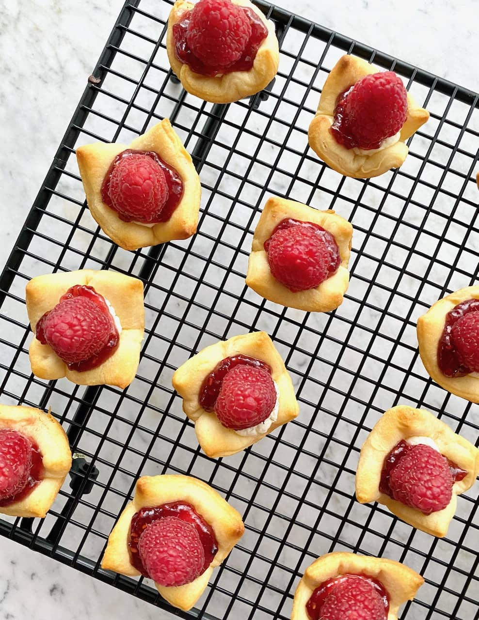 raspberry goat cheese bites cooling on a baking rack.